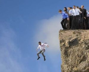 businessman_jumping_off_cliff_while_co-workers_watch_BLD079368